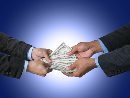 payola: Businessman recieving the money offered by businessman on dark blue background,include clipping path