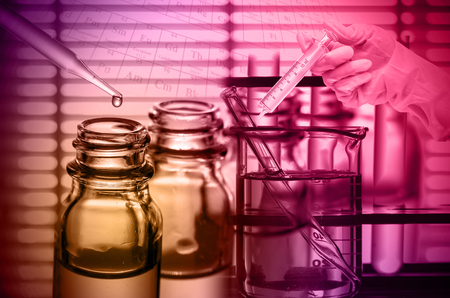 lighting technician: Chemical Laboratory,scientist dropping the reagent into test flask