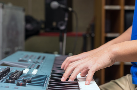ivories: hands playing the keyboard or piano, focus middle finger