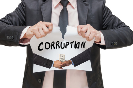 shake up: Businessman ripping up the CORRUPTION sign with Hand shake between a businessman and dollar money on white background