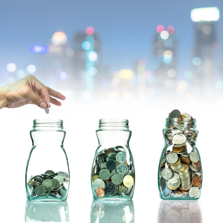 investment ideas: Hand putting mix coins in clear bottle on cityscape photo blurred bokeh background,Business investment growth concept