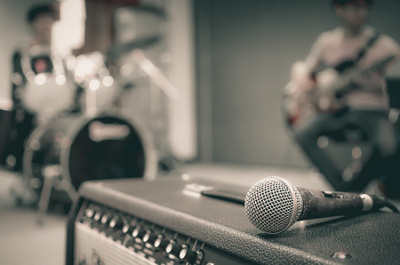 sound studio: Closeup of microphone on musician blurred background Stock Photo