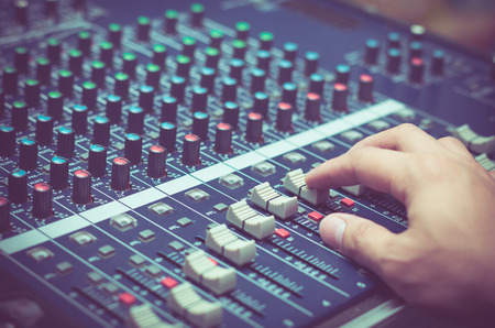 Hand adjusting audio mixer Stock Photo