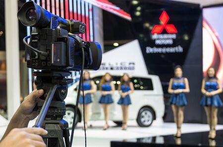 vdo: BANGKOK - APRIL 3 : Hand holding the VDO camera monitoring the stage show of mitsubishi on the stage blurred bokeh background in The 36 th Bangkok International Motorshow , on April. 3, 2015 in Bangkok, Thailand