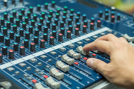 Hand adjusting audio mixer Banco de Imagens