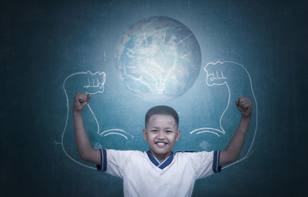 Asian strong children against blackboard in classroom, Education concept.  photo
