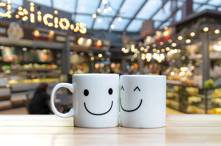 sweet shop: Two happy cups on coffee store blur background