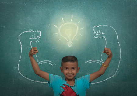 asian strong children against blackboard in classroom, Education concept photo