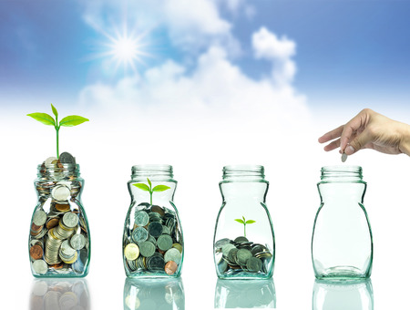 Hand putting mix coins and seed in clear blottle on blurred blue sky with cloud background,Business investment growth concept Stock Photo