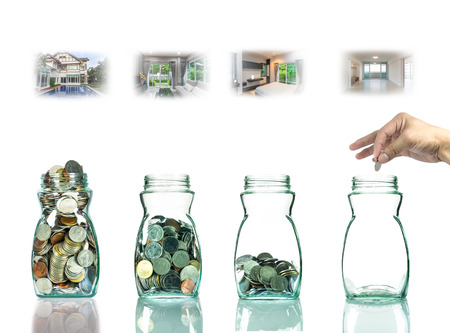 clear bottle: Hand putting mix coins in clear bottle with step of construction house ,Business investment growth concept Stock Photo