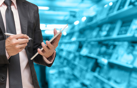 Businessman using the tablet on Abstract blurred photo of book store background, blur color tone photo