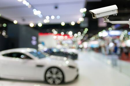 show room: CCTV security camera on monitor the Abstract blurred photo of motor show, car show room Stock Photo