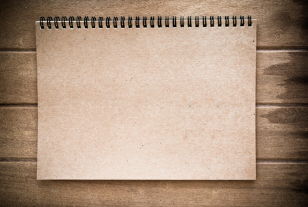 Brown color notebook on wood background, vintage tone