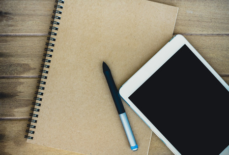 Notebook with tablet and pen on wooden table photo