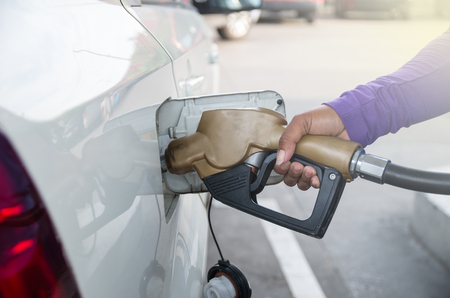 energize: Hand hold Fuel nozzle to add fuel in car at filling station