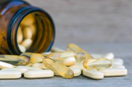 witaminy: Pigułki lub witaminy w butelkach medycyny na tle drewna Zdjęcie Seryjne