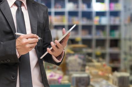 gerente: Hombre de negocios usando la tableta en Resumen foto borrosa de la tienda de libros de fondo