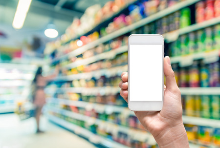 Female hand holding mobile smart phone on Supermarket blur background, business concept Imagens