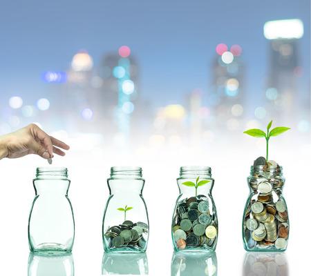 crecimiento planta: Mano poner monedas de mezcla y semilla en botella transparente sobre paisaje urbano foto borrosa bokeh de fondo, el concepto de crecimiento de la inversi�n de negocios