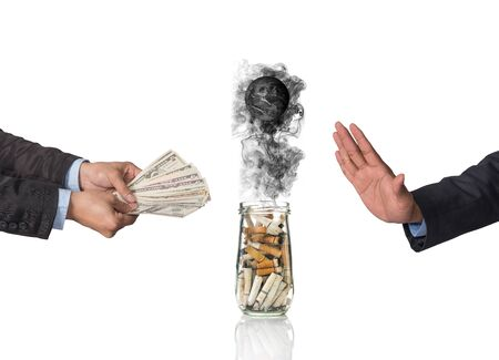 burning money: Hand refusing the money offered with Cigarette butt in bottle with smoke Burning the world Stock Photo