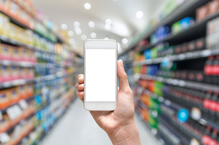grocery shelves: Female hand holding mobile smart phone on Supermarket blur background, business concept Stock Photo