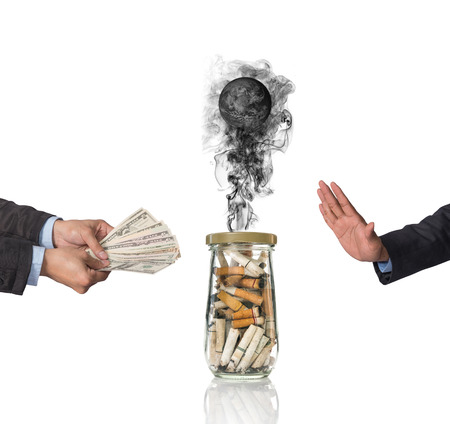 burning money: Hand refusing the money offered with Cigarette butt in bottle with smoke Burning the world, world no tobacco day