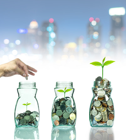 investment concept: Hand putting mix coins and seed in clear bottle on cityscape photo blurred bokeh background,Business investment growth concept
