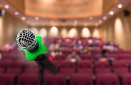 attendee: Microphone with Abstract blurred photo of conference hall or meeting room with attendee background