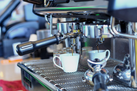 cool: Coffee machine making espresso shot in a cafe shop, blue cool tone Stock Photo