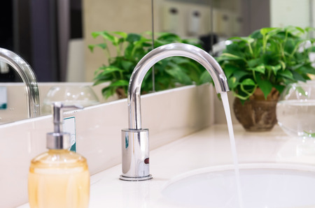 tap: Chrome faucet with washbasin in modern bathroom
