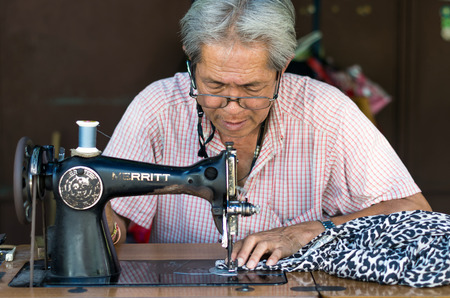 asian old man: BANGKOK, THAILAND - JUNE 04: Asian old man Seamstress are sewing the clothes by vintage sewing machine on June 04, 2015 at bangkok, Thailand