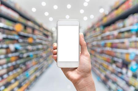 supermercado: Mano femenina que sostiene el teléfono móvil inteligente en segundo plano borroso supermercado, concepto de negocio
