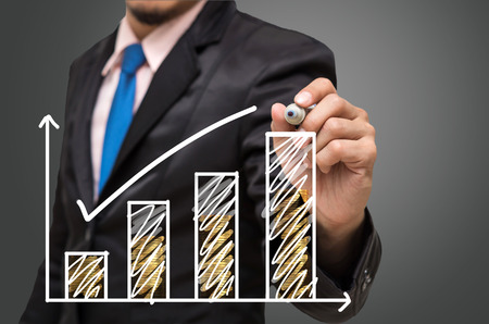 investment concept: Businessman hand writing a graph with gold coin on gray background, Business investment concept