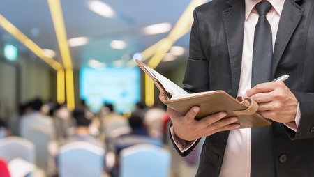 media event: Businessman writing the note book on the Abstract blurred photo of conference hall or seminar room with attendee background Stock Photo