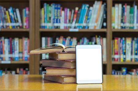 bookshelf digital: old book on the desk in library with tablet