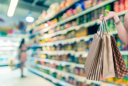 shoping: Holding shoping bags by hand on Supermarket with customer blur background and bokeh, Miscellaneous Product shelf