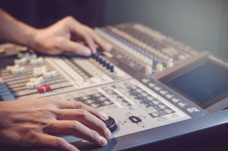 adjusting: Hand adjusting audio mixer Stock Photo