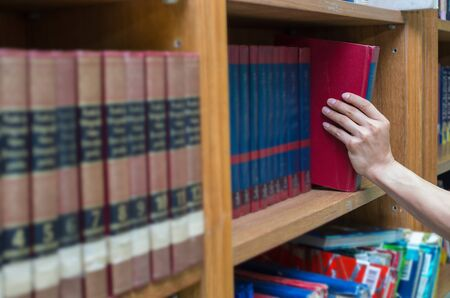 choose university: closeup hand selecting book from a bookshelf in library Stock Photo