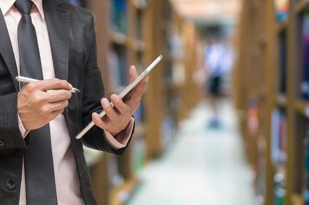 biblioteca: Hombre de negocios usando la tableta en la foto borrosa abstracta de la biblioteca con el fondo del estudiante