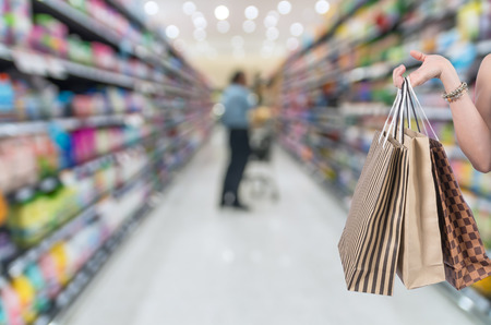 shoping: Holding shoping bags by hand on Supermarket blur background with bokeh, Miscellaneous Product shelf