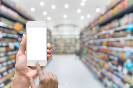 Female hand holding mobile smart phone on Supermarket blur background, business concept Stock Photo