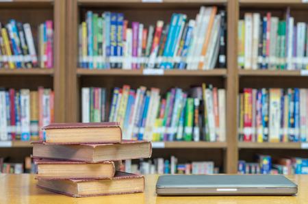 biblioteca: viejo libro sobre la mesa en la biblioteca con la tableta