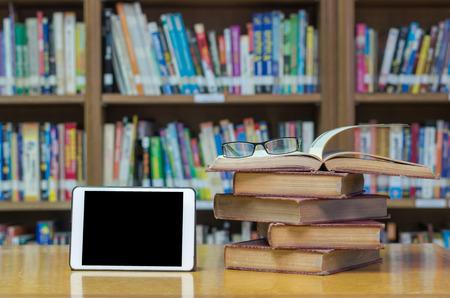태블릿 및 안경 라이브러리에서 책상에 오래 된 책 스톡 콘텐츠