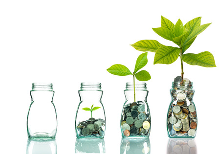Mix coins and seed in clear bottle on white background,Business investment growth concept Archivio Fotografico