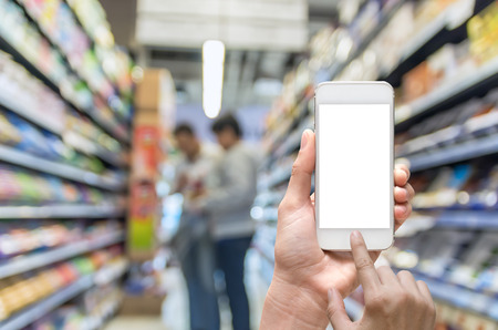 oncept: Female hand holding mobile smart phone on Supermarket blur background, business concept Stock Photo
