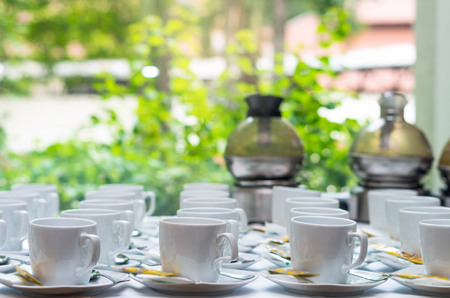 Many rows of white coffee cup with saucer and teaspoon on table and coffee maker background