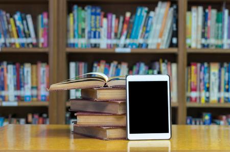 staré knihy na stole v knihovně s tabletem