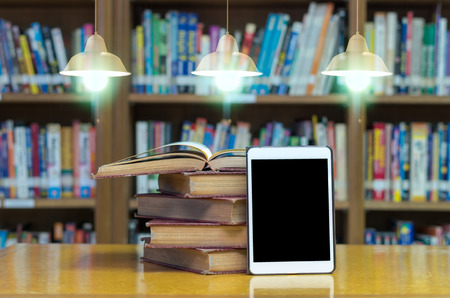 old book on the desk in library with tablet and Luxury lighting decoration 版權商用圖片 - 44166158