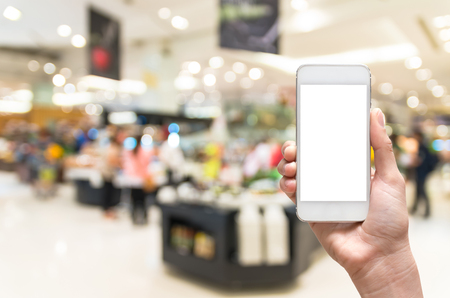 oncept: Female hand holding mobile smart phone on salad bar store blur background, business concept