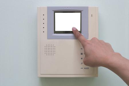 intercom: Human finger pushing button of video intercom equipment
